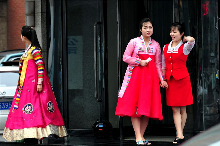Restaurant waitresses dressed in Korean ethnic garb ready to welcome customers in Dandong, Liaoning province, on May 1. (YU HAIYANG/FOR CHINA DAILY)