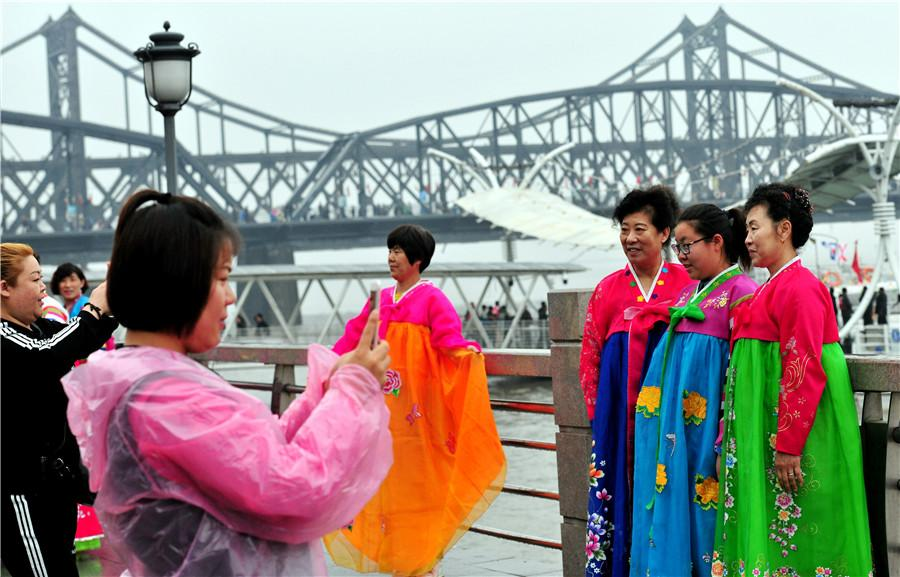 Tourists dressed in Korean ethnic garb pose in front of the Yalu River in Dandong, Liaoning province, on May 1. (YU HAIYANG/FOR CHINA DAILY)