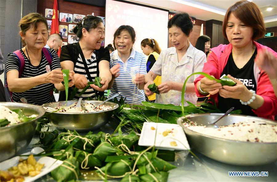 Volunteers make zongzi, a pyramid-shaped dumpling made of glutinous rice wrapped in bamboo or reed leaves, for the elderly persons of no family to celebrate the Duanwu Festival at a community in Zhenjiang City, east China\'s Jiangsu Province, June 11, 2018. (Xinhua/Shi Yucheng)