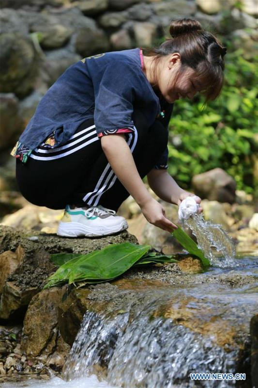 A woman cleans leaves for making Zongzi, a pyramid-shaped dumpling made of glutinous rice wrapped in bamboo or reed leaves, to greet the upcoming Dragon Boat Festival in a rivulet of Zhangjiajie City, central China\'s Hunan Province, June 11, 2018. (Xinhua/Wu Yongbing)