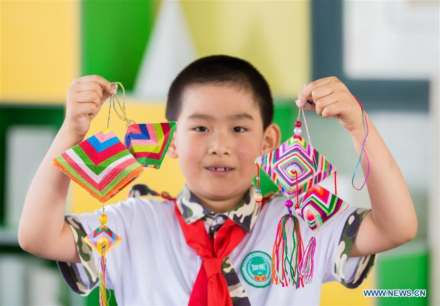 A pupil shows sachets in the shape of Zongzi, pyramid-shaped dumplings made of glutinous rice wrapped in bamboo or reed leaves, to greet the upcoming Dragon Boat Festival at a primary school in Hohhot, capital of north China\'s Inner Mongolia Autonomous Region, June 12, 2018. (Xinhua/Ding Genhou)