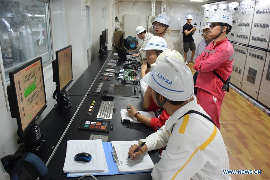 Staff members work at the control room on Tian Kun Hao, a Chinese-built dredging vessel, the largest of its kind in Asia, June 7, 2018. Tian Kun Hao, constructed by Tianjin Dredging Co. Ltd., a subsidiary of China Communication Construction Co., Ltd. (CCCC), finished its first sea trial. The 140-meter-long vessel, with the designed capacity to dredge 6,000 cubic meters per hour, can dig as deep as 35 meters under the sea floor. (Xinhua/Mao Zhenhua)