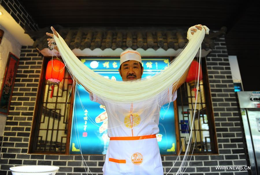 Quan Fujian pulls noodles at his restaurant in Yantai City, east China\'s Shandong Province, June 7, 2018. Fushan noodle is a traditional dish which is popular in Shandong Province. The noodle is hand pulled and cooked with various sauces and broths. The making of Fushan noodle was listed as a provincial intangible cultural heritage of Shandong in 2013. (Xinhua/Ren Pengfei)