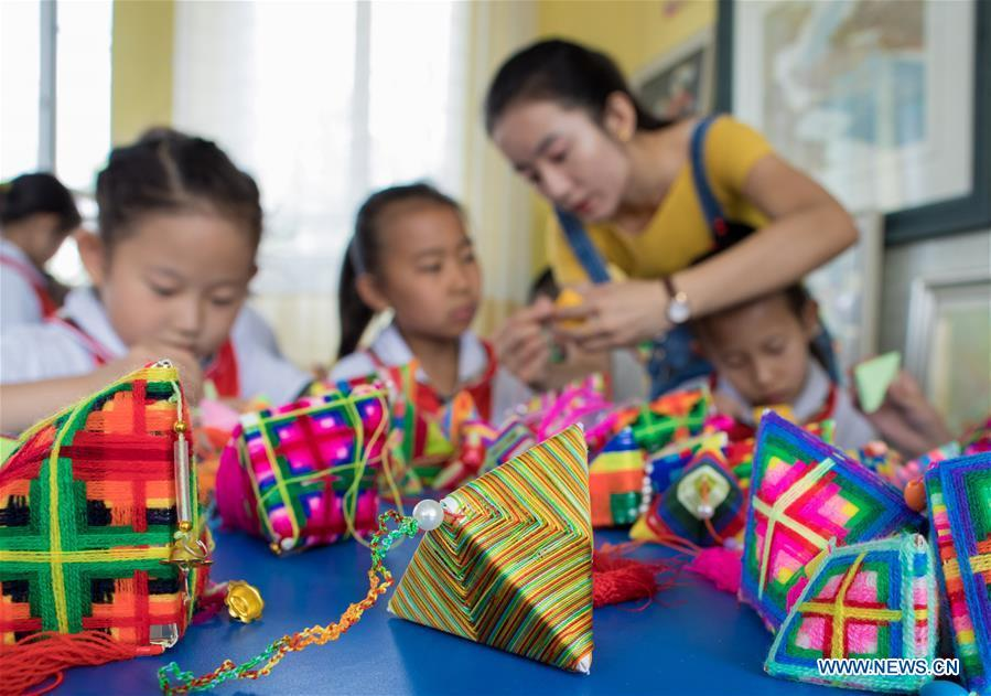 Pupils make sachets in the shape of Zongzi, pyramid-shaped dumplings made of glutinous rice wrapped in bamboo or reed leaves, to greet the upcoming Dragon Boat Festival at a primary school in Hohhot, capital of north China\'s Inner Mongolia Autonomous Region, June 12, 2018. (Xinhua/Ding Genhou)