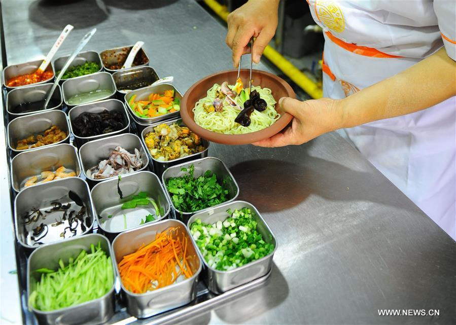 Quan Fujian prepares meals for customers at his restaurant in Yantai City, east China\'s Shandong Province, June 7, 2018. Fushan noodle is a traditional dish which is popular in Shandong Province. The noodle is hand pulled and cooked with various sauces and broths. The making of Fushan noodle was listed as a provincial intangible cultural heritage of Shandong in 2013. (Xinhua/Ren Pengfei)