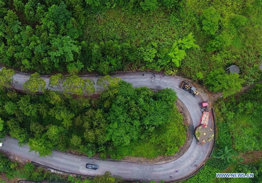 A truck carrying a giant bronze drum runs on a mountain road in Huanjiang Maonan Autonomous County, south China\'s Guangxi Zhuang Autonomous Region, June 12, 2018. The diameter of the drum is over six meters. It will be conveyed to Huazhumao plaza in Huanjiang. (Xinhua/Gao Dongfeng)