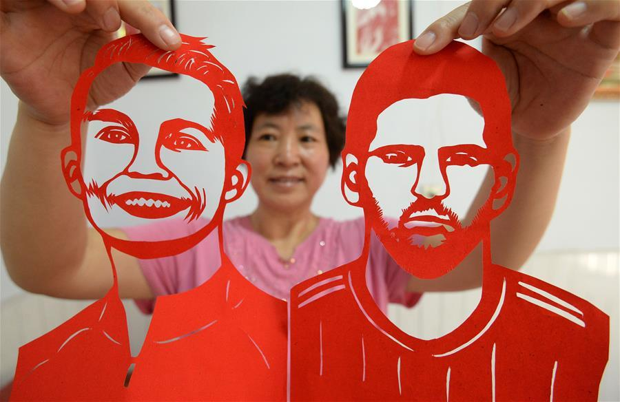 Craftswoman Feng Shiping shows paper-cutting works of football players Lionel Messi and Cristiano Ronaldo in Handan, north China\'s Hebei Province, June 12, 2018, to greet the FIFA World Cup. (Xinhua/Hao Qunying)