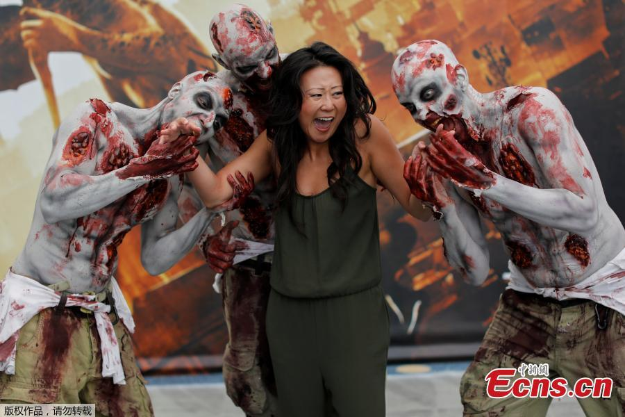 An attendee poses for a picture with a zombie at E3, the world\'s largest video game industry convention in Los Angeles, California, U.S., June 12, 2018. (Photo/Agencies)