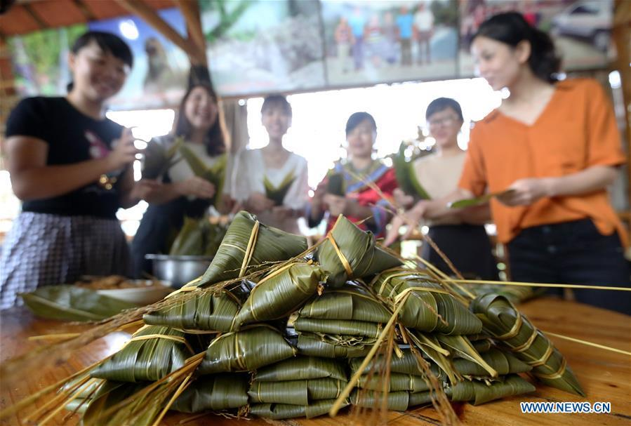 Visitors and residents make colorful Zongzi, pyramid-shaped dumplings made of glutinous rice wrapped in bamboo or reed leaves, to greet the upcoming Dragon Boat Festival in Rong\'an County, south China\'s Guangxi Zhuang Autonomous Region, June 12, 2018. (Xinhua/Tan Qinghe)