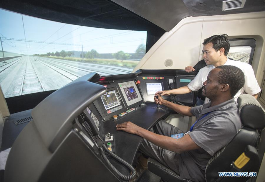 A railway executive from Kenya experiences a simulation of high-speed train driving at a training base for high-speed railway staff in Wuhan, central China\'s Hubei Province, June 12, 2018. Altogether 63 railway executives from 13 countries including Thailand, Sri Lanka and Laos visited the training base Tuesday. (Xinhua/Xiao Yijiu)