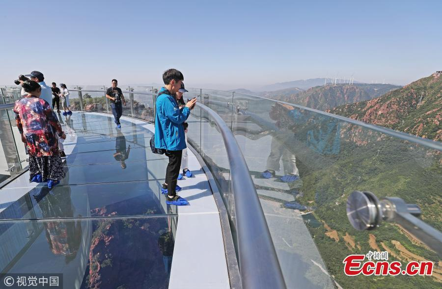 A skywalk is ready to open to the public in Fuxi Mountain scenic area in Xinmi City, Central China's Henan Province, June 12, 2018. Built with 3,000 tons of steel, the U-shaped cantilevered glass walkway is 360 meters above the canyon floor and extends 30 meters past the cliff edge. (Photo/VCG)