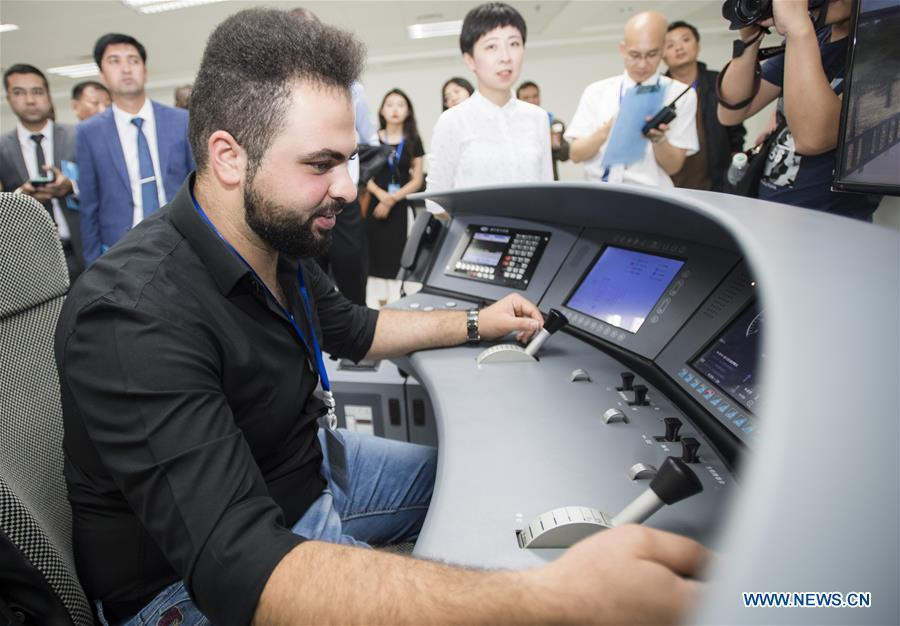 A railway executive from Jordan experiences a simulation of high-speed train driving at a training base for high-speed railway staff in Wuhan, central China\'s Hubei Province, June 12, 2018. Altogether 63 railway executives from 13 countries including Thailand, Sri Lanka and Laos visited the training base Tuesday. (Xinhua/Xiao Yijiu)