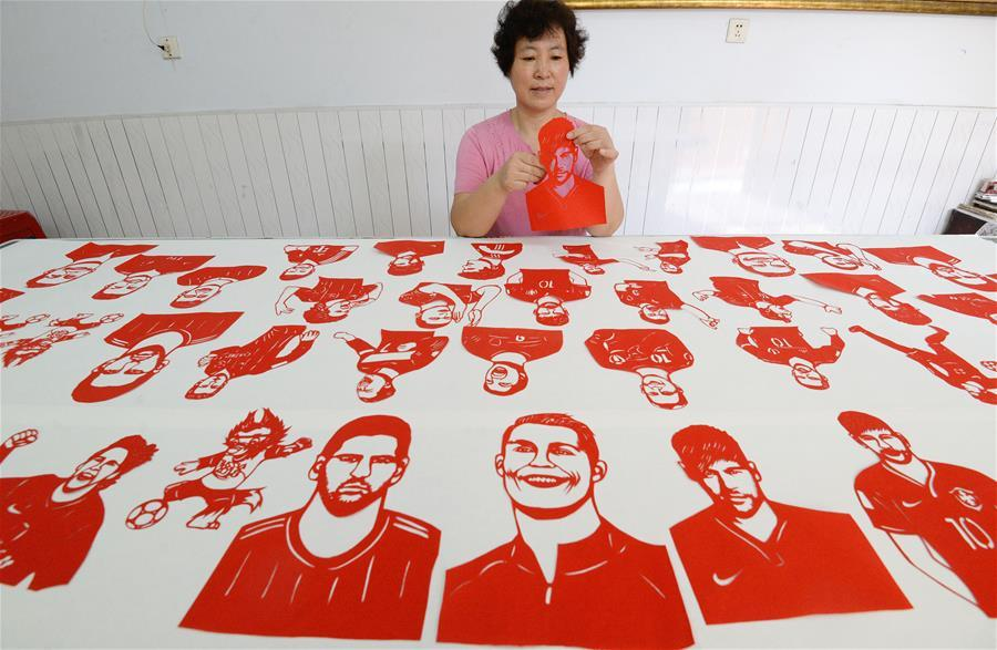 Craftswoman Feng Shiping makes paper-cutting works to greet the FIFA World Cup in Handan, north China\'s Hebei Province, June 12, 2018. (Xinhua/Hao Qunying)