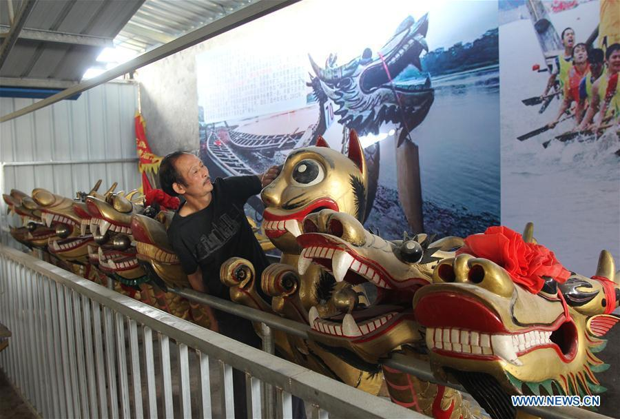 Folk artist Chen Bingshou displays the dragon head for the bow of a dragon boat in Daoxian County of Yongzhou City, central China\'s Hunan Province. Chen, 56, has been engaged in making dragon head for over 40 years. Every year, June is the busiest time for Chen as the demand for the dragon head is strong ahead of the dragon boat festival. Each dragon weighs about 15 kilograms and it takes Chen about 12 days to finish. (Xinhua/He Hongfu)