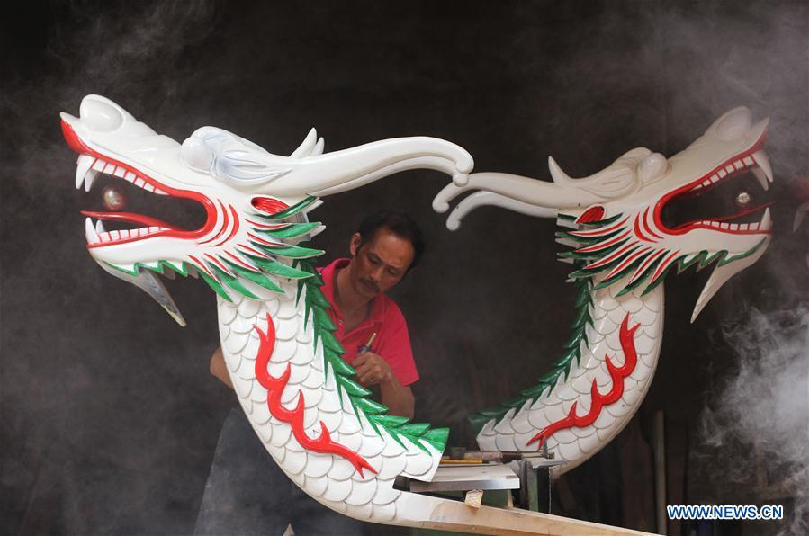 Folk artist Chen Bingshou displays a dragon boat model in Daoxian County of Yongzhou City, central China\'s Hunan Province. Chen, 56, has been engaged in making dragon head for over 40 years. Every year, June is the busiest time for Chen as the demand for the dragon head is strong ahead of the dragon boat festival. Each dragon weighs about 15 kilograms and it takes Chen about 12 days to finish. (Xinhua/He Hongfu)