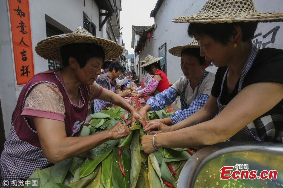Villagers make a special zongzi - traditionally a pyramid-shaped dumpling made of glutinous rice wrapped in bamboo or reed leaves - to welcome the upcoming Dragon Boat Festival in Qiaoxi Village, Lishui City, East China's Zhejiang Province, June 12, 2018. It took 50 people nearly 13 hours to make the cylinder zongzi, which was 20.18 meters long and 10 centimeters in diameter, and used 100 kilograms of sticky rice, 20 kilograms of preserved meat and thousands of leaves. (Photo/VCG)