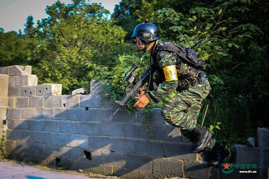 A soldier rushes through a gap in the wall in the operation area during the week-long rigorous training starting from June 11, 2018. (Photo/81.cn) Soldiers from the Ningbo, Shaoxing, Zhoushan and Taizhou divisions of the Armed Police Force in East China's Zhejiang Province took part in a week-long rigorous training program starting from June 11, 2018. The training included long marches, simulated battles, mountain climbing and a manhunt on the water.