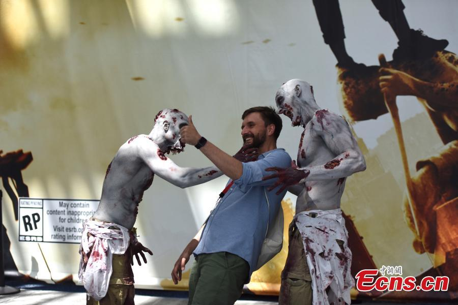 An attendee poses for a picture with zombies at E3, the world\'s largest video game industry convention in Los Angeles, California, U.S., June 13, 2018. (Photo: China News Service/Zhang Shuo)