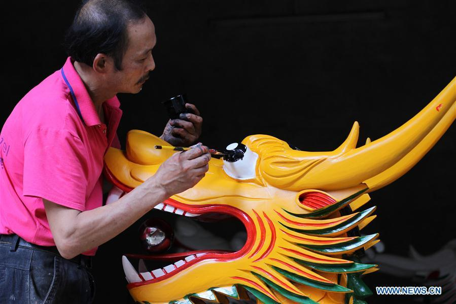 Folk artist Chen Bingshou (1st R) installs the dragon head on the boat with others in Daoxian County of Yongzhou City, central China\'s Hunan Province. Chen, 56, has been engaged in making dragon head for over 40 years. Every year, June is the busiest time for Chen as the demand for the dragon head is strong ahead of the dragon boat festival. Each dragon weighs about 15 kilograms and it takes Chen about 12 days to finish. (Xinhua/He Hongfu)