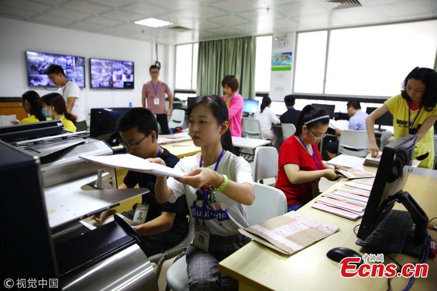 Teachers grade test papers of the national college entrance exam, known as gaokao, at Hainan Normal University in Haikou City, South China's Hainan Province, June 12, 2018. The province's 699 teachers will be responsible for grading gaokao test papers from June 14 to 20 at well-guarded sites. (Photo/VCG)