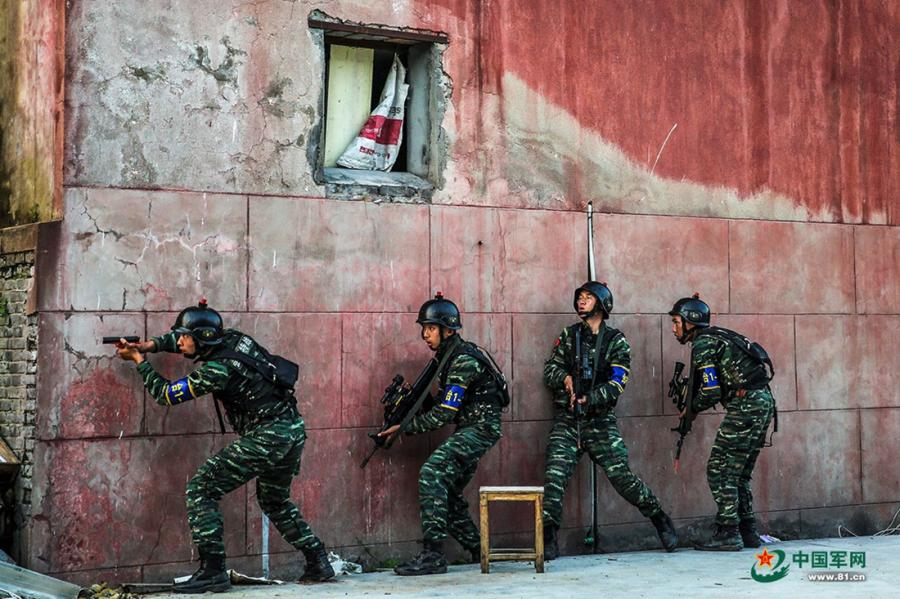 A group of soldiers cautiously move along a wall as they move around the operation area during the week-long rigorous training starting from June 11, 2018. (Photo/81.cn)