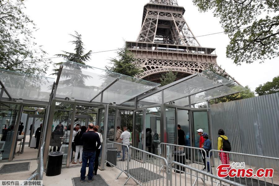 Tourists and visitors queue to pass the security check at the entrance to the new glass fence around the Eiffel Tower in Paris, France, June 14, 2018. Paris authorities are building a permanent security belt around the Eiffel Tower, replacing the current fencing around it with more visually appealing glass walls. (Photo/Agencies)