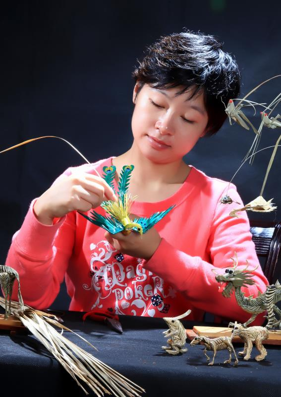 Artist Zhou Jialin works on a bird. (Photo by Song Guoqing/China Daily)