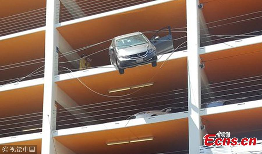 Photo taken on June 11, 2018 shows a tourist rescued a motorist whose car was left dangling off the fifth floor of a car park in Santa Monica, California. The female driver, reportedly in her 60s, came close to driving off the edge of the building after accidentally pushing the accelerator, local media reported. (Photo/Agencies)