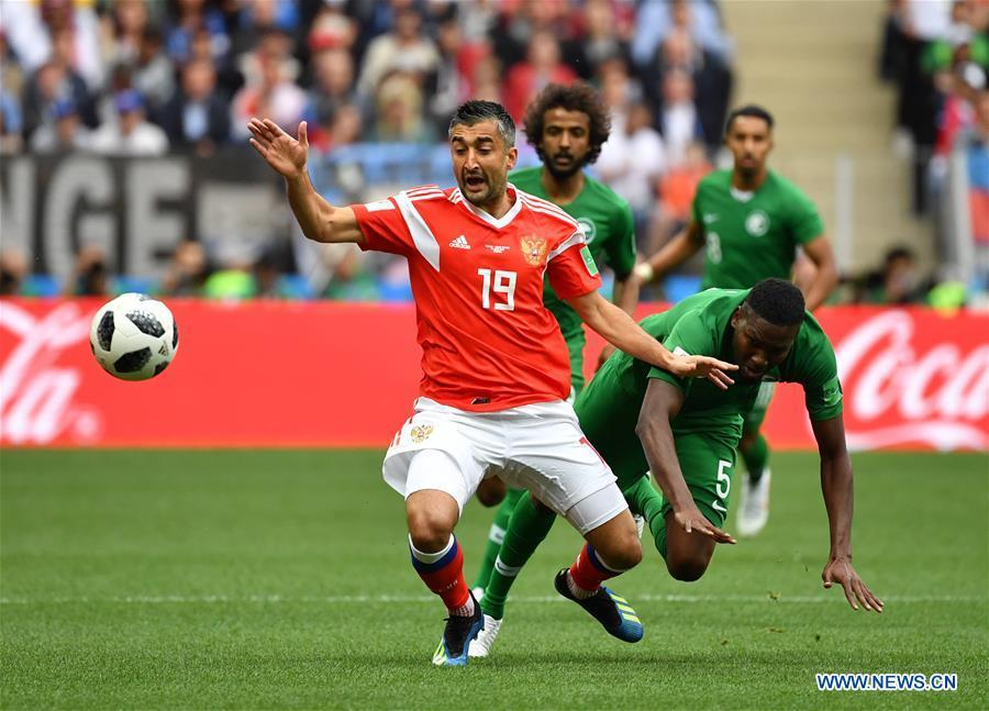 Russia\'s Alexandr Samedov (L) vies with Saudi Arabia\'s Omar Othman during the opening match of the 2018 FIFA World Cup in Moscow, Russia, on June 14, 2018. (Xinhua/Cao Can)