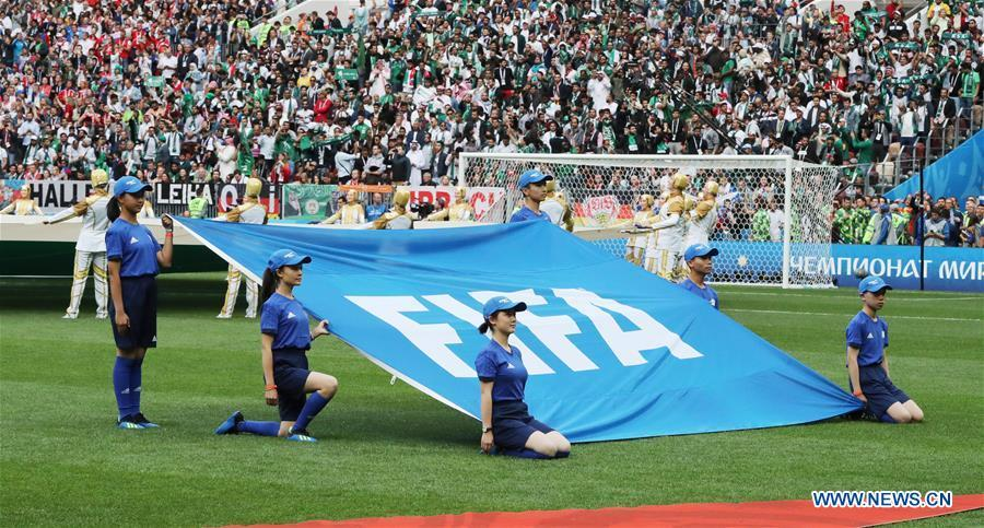 Chinese caddies hold a FIFA flag before the opening match of the 2018 FIFA World Cup in Moscow, Russia, on June 14, 2018. (Xinhua/Xu Zijian)