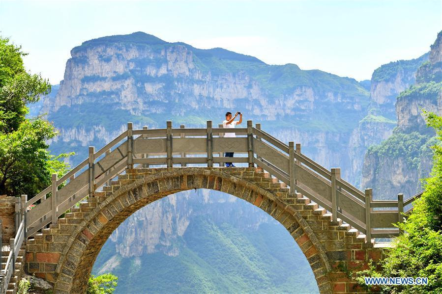A tourist takes photos in Shenlongwan scenic area in Changzhi City, north China\'s Shanxi Province, June 13, 2018. A 1,526-meter-long road was built along the cliffs to connect isolated Shenlongwan to the outside. The construction of this miraculous road lasted for fifteen years from 1985 to 2000, and was built purely by villagers of Shenlongwan. Thanks to this road, villagers here now cast off poverty by developing tourism. (Xinhua/Cao Yang)