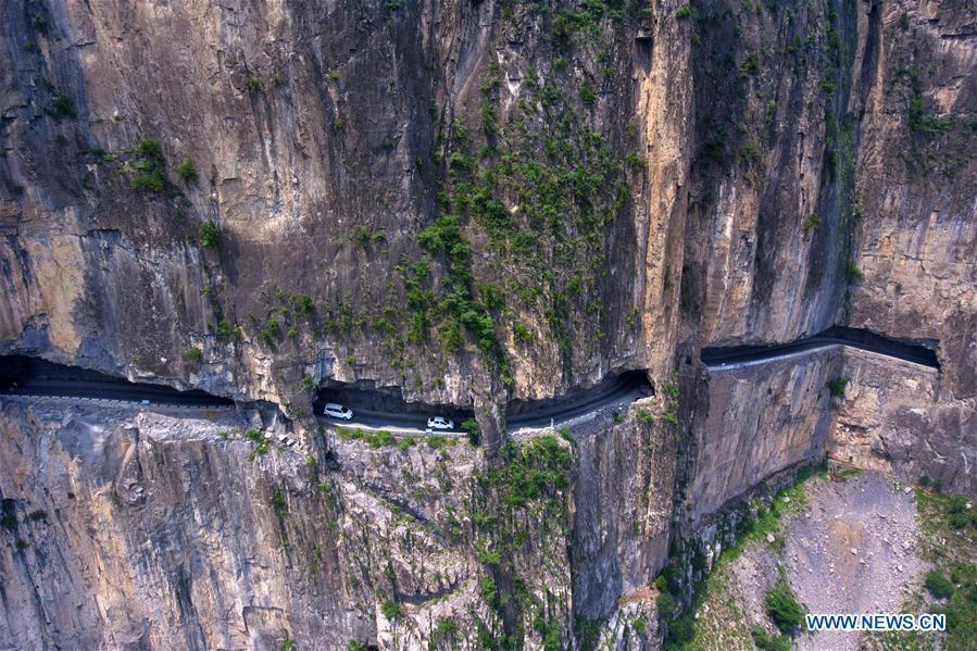 Aerial photo taken on June 13, 2018 shows cars running on a road in cliffs in Shenlongwan Village in Changzhi City, north China\'s Shanxi Province. A 1,526-meter-long road was built along the cliffs to connect isolated Shenlongwan to the outside. The construction of this miraculous road lasted for fifteen years from 1985 to 2000, and was built purely by villagers of Shenlongwan. Thanks to this road, villagers here now cast off poverty by developing tourism. (Xinhua/Cao Yang)