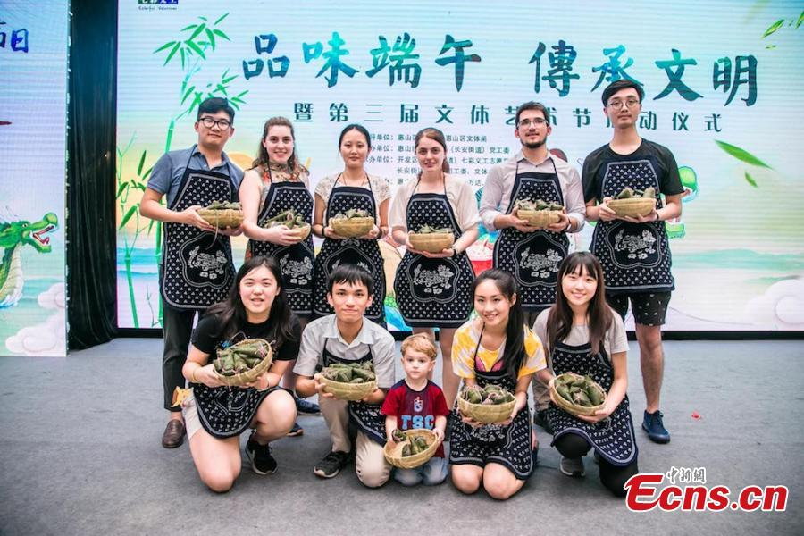 A group of overseas students and expats gathered at Huishan economic development zone in Wuxi, Jiansu Province to learn how to make zongzi, the palm-sized snack made of glutinous rice wrapped in reed leaves, to the upcoming Dragon Boat Festival, June 15, 2018. (Photo: China News Service/Sun Quan)