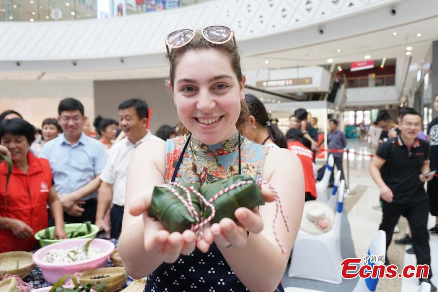 A girl shows self-made zongzi, the palm-sized snack made of glutinous rice wrapped in reed leaves, at a group event at Huishan economic development zone in Wuxi, Jiansu Province, June 15, 2018. (Photo: China News Service/Sun Quan)