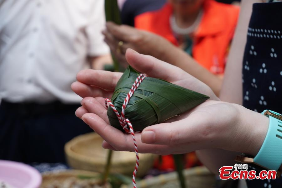 A group of overseas students and expats gathered at Huishan economic development zone in Wuxi, Jiansu Province to learn how to make Zongzi, the palm-sized snack made of glutinous rice wrapped in reed leaves, June 15, 2018, to celebrate the upcoming Dragon Boat Festival. (Photo: China News Service/Sun Quan)