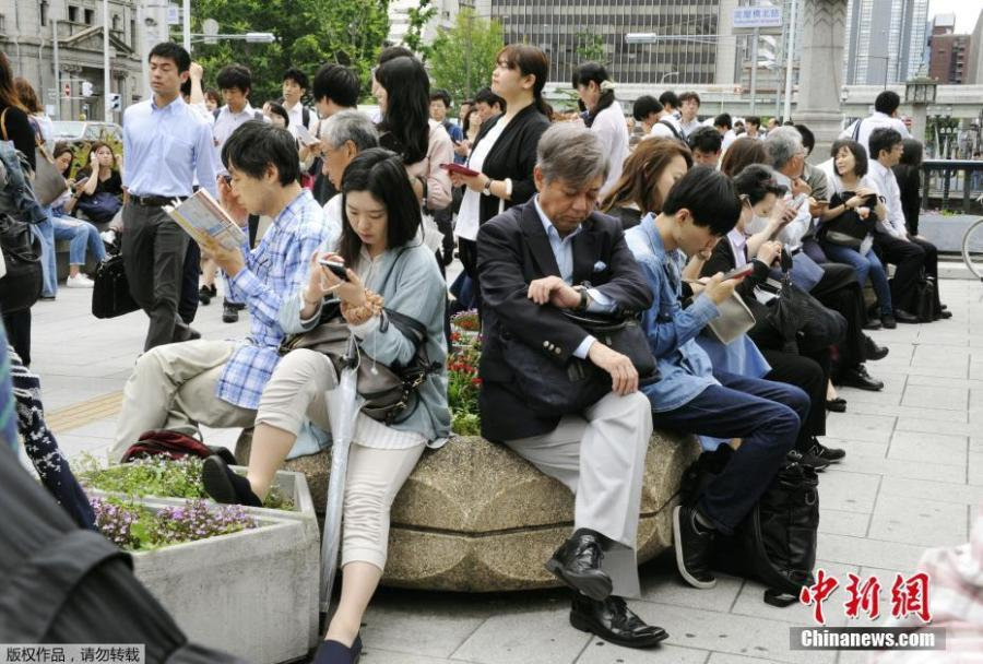 People wait for the resume of operation of train service nearby Yodoyabashi station in Osaka, Osaka prefecture, western Japan, June 18, 2018. (Photo/China News Service)
