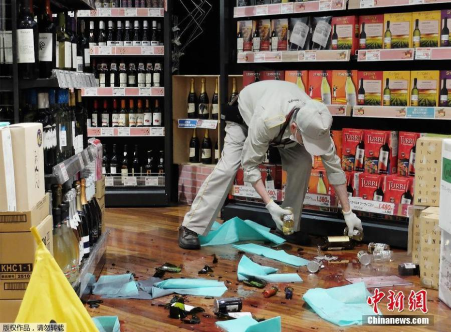 A shop employee clears broken bottles following an earthquake in Osaka, Japan on June 18, 2018.  (Photo/China News Service)