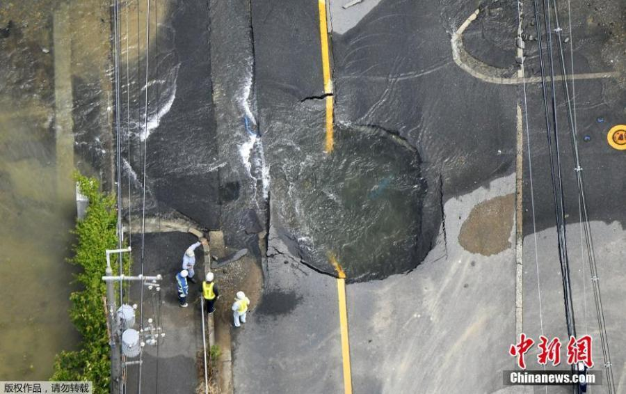 Water flows out from cracks in a road damaged by an earthquake in Takatsuki, Osaka prefecture, western Japan, June 18, 2018. (Photo/China News Service)