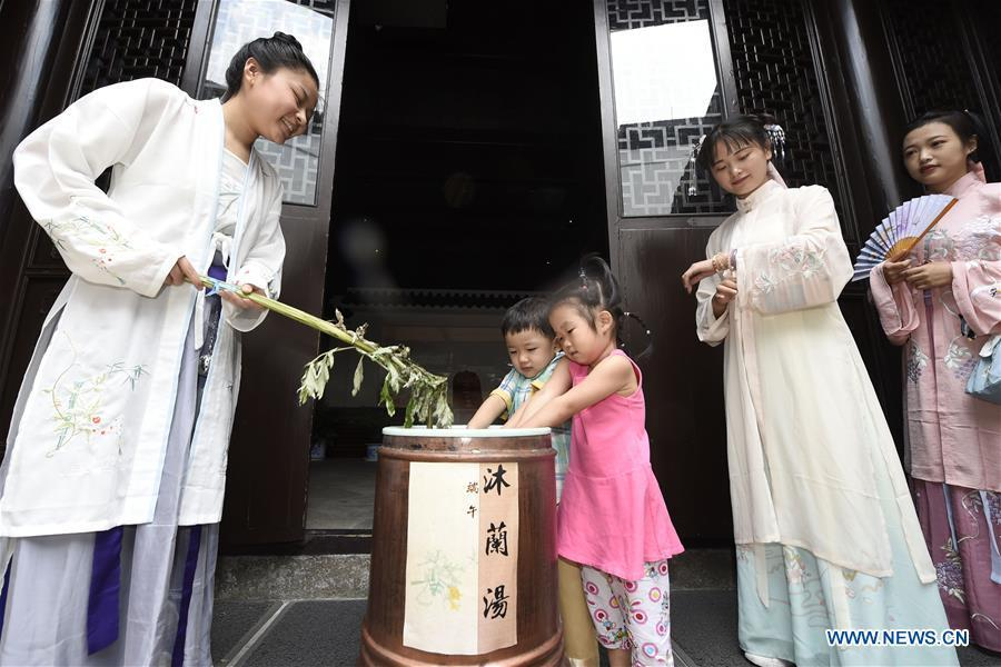 Children experience traditional customs at the Museum of Hangzhou Local Chronicles in Hangzhou, capital of east China\'s Zhejiang Province, June 17, 2018. People enjoy their holiday time during the Dragon Boat Festival. (Xinhua/Li Zhong)