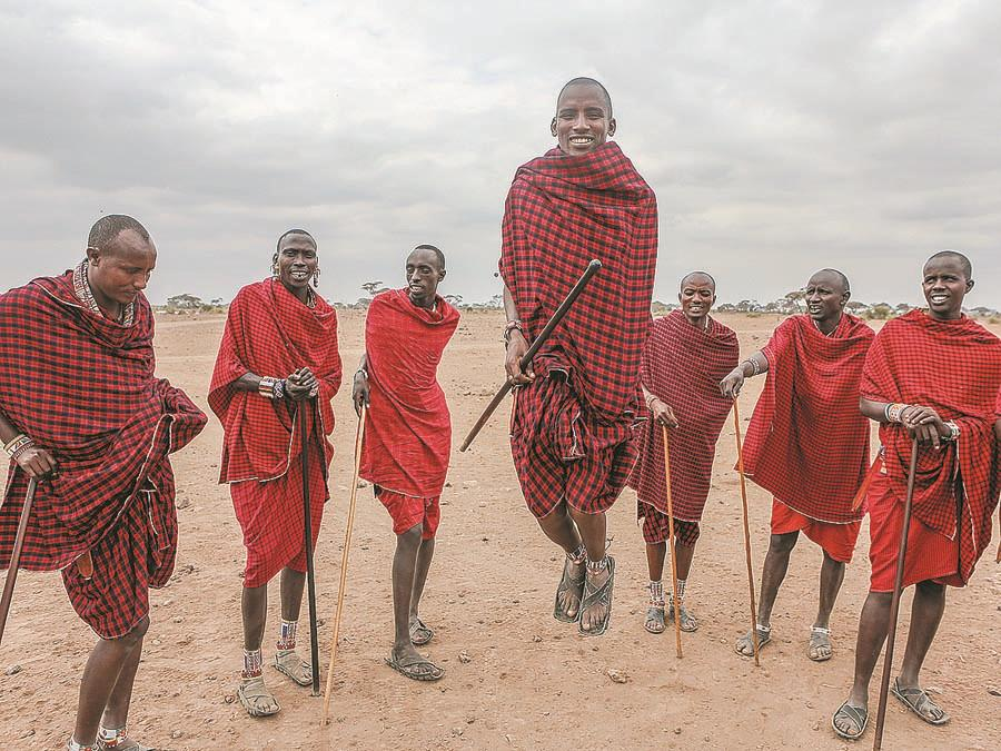 Masai men sing and welcome visitors to a village in the Amboseli National Park. (PHOTO BY XIE SONGXIN/CHINA DAILY)