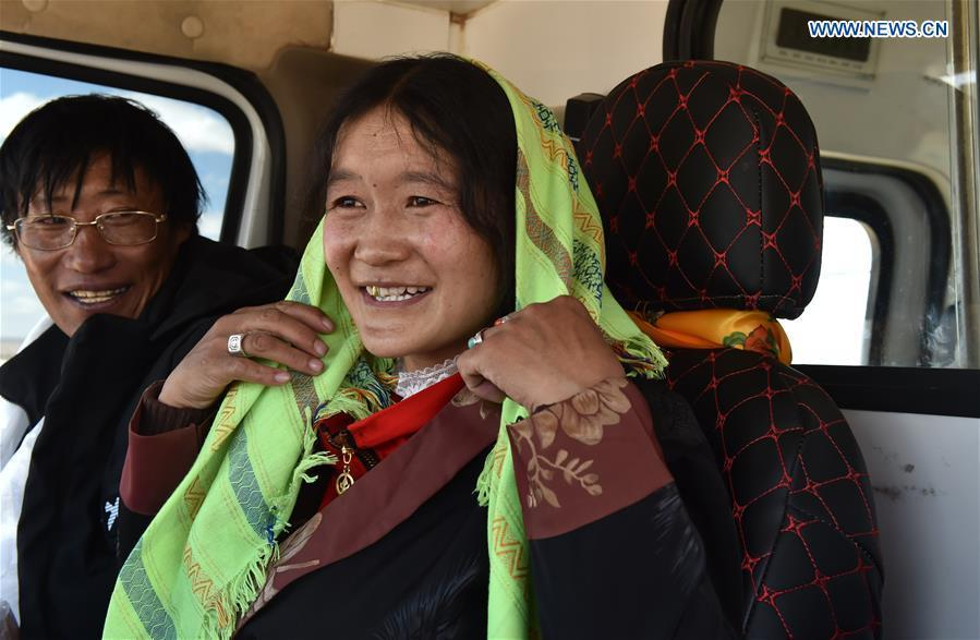 Villagers sit in a coach which will carry them from Nyima County of Nagqu to a new settlement in Lhasa during a relocation program with environmental purposes, southwest China\'s Tibet Autonomous Region, June 17, 2018. A total of 1,102 residents have been relocated to a new settlement in Lhasa to make their old neighbourhoods accessible to wild animals in the Qiangtang National Nature Reserve. Completed on Monday, the relocation marked the first such program carried out for the sake of environmental protection in areas at high altitudes in Tibet Autonomous Region. (Xinhua/Chogo)