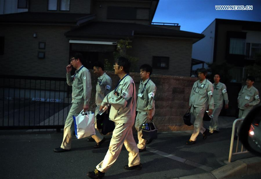 Engineers walk at a street in Takatsuki, Osaka, Japan, on June 18, 2018. At least three people have been confirmed dead and more than 90 others injured as a result of a 6.1 magnitude earthquake striking Osaka prefecture in western Japan on Monday morning. (Xinhua/Ma Ping)