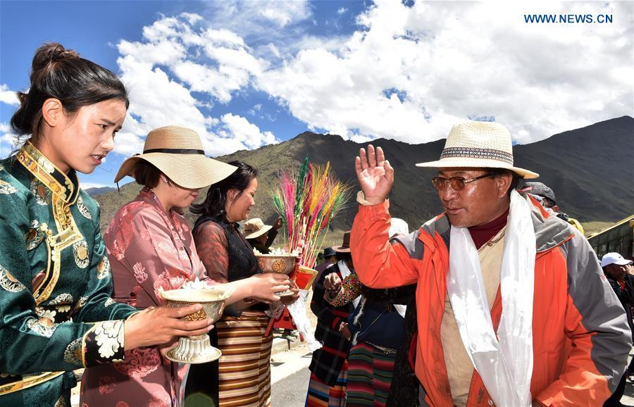 Villagers who have moved from Nyima County of Nagqu during a relocation program with environmental purposes are welcomed at their new settlement in Lhasa, southwest China\'s Tibet Autonomous Region, June 18, 2018. A total of 1,102 residents have been relocated to a new settlement in Lhasa to make their old neighbourhoods accessible to wild animals in the Qiangtang National Nature Reserve. Completed on Monday, the relocation marked the first such program carried out for the sake of environmental protection in areas at high altitudes in Tibet Autonomous Region. (Xinhua/Chogo)