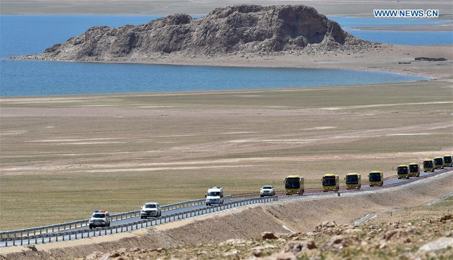 A motorcade of coaches carry villagers from Nyima County of Nagqu to a new settlement in Lhasa during a relocation program with environmental purposes in southwest China\'s Tibet Autonomous Region, June 17, 2018. A total of 1,102 residents have been relocated to a new settlement in Lhasa to make their old neighbourhoods accessible to wild animals in the Qiangtang National Nature Reserve. Completed on Monday, the relocation marked the first such program carried out for the sake of environmental protection in areas at high altitudes in Tibet Autonomous Region. (Xinhua/Chogo)