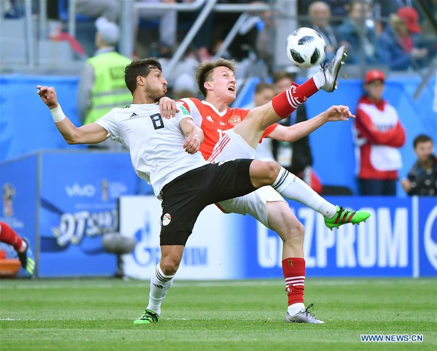 Aleksandr Golovin (R) of Russia vies with Tarek Hamed of Egypt during a Group A match between Russia and Egypt at the 2018 FIFA World Cup in Saint Petersburg, Russia, June 19, 2018. (Xinhua/Li Ga)
