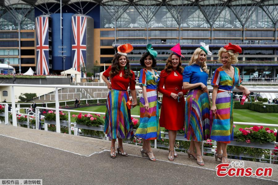 Racegoers pose for a photograph at Royal Ascot, Britain, June 19, 2018. Racegoers adorned their statement hats with feathers and flowers in one of Britain\'s most well-known racecourses. (Photo/Agencies)