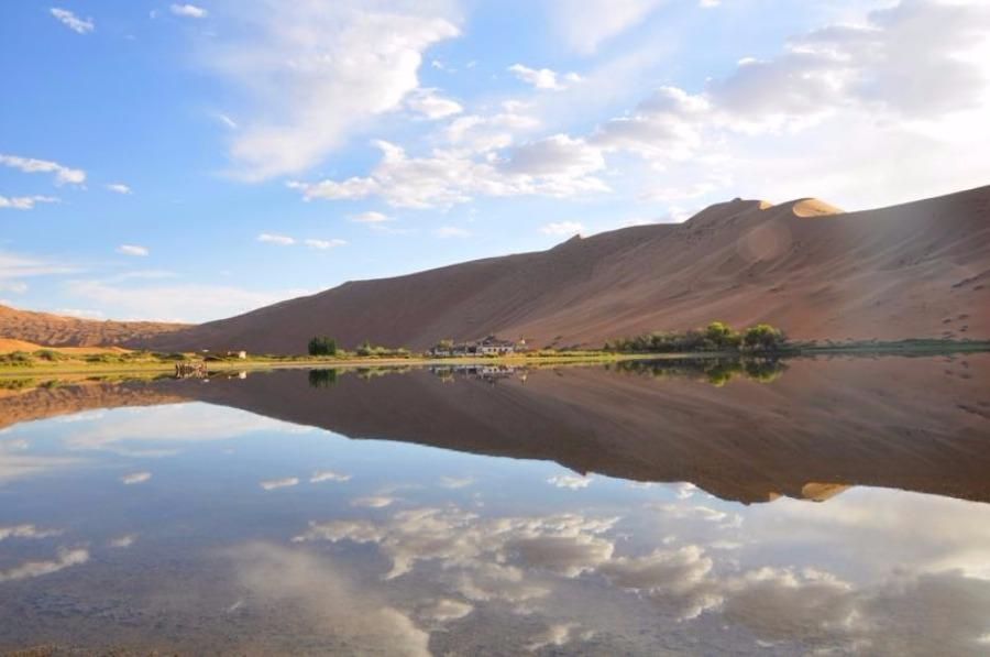 Scenery from the Badain Jaran desert in Alshaa league, North China\'s Inner Mongolia autonomous region. Sapphire-blue lakes coexist with high and low sand hills, presenting an interesting blend of barren and lush landscapes. (Photo/China Daily)
