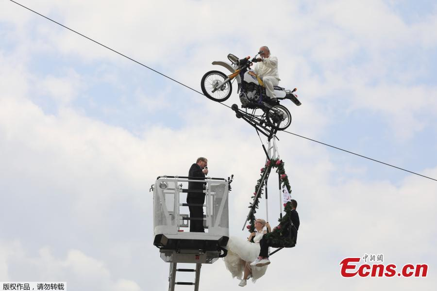 Pastor Stefan Gierung, left, stands in a cage atop of a fire service ladder in front of bride Nicole Backhaus, center, and groom Jens Knorr, right, both sitting in a swing dangling under a motorcycle with artist Falko Traber, top, during the wedding ceremony atop a tightrope in Stassfurt, Germany, June 16, 2018. (Photo/Agencies)