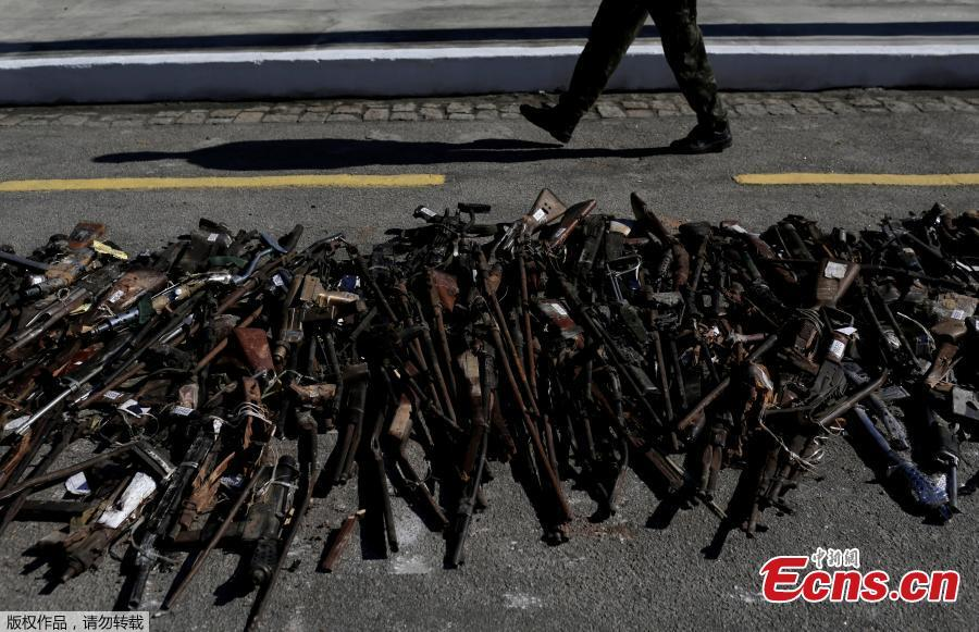 A Brazilian Army soldier walks past by guns seized from criminals by armed forces before being destroyed in Rio de Janeiro, Brazil, June 20, 2018. The Brazilian army invited the media Wednesday to observe the destruction of 8,549 firearms seized from criminals, handed in voluntarily, or retired from police arsenals. (Photo/Agencies)