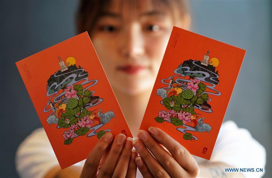 A staff member shows postcards with a creative design based on China\'s traditional 24 solar terms at a souvenir shop in Beihai Park, Beijing, capital of China, June 20, 2018. The 24 solar terms are a list of terms central to a calendar created in ancient China. Based on the movement of the sun, the calendar divides the year into 24 segments to guide farming over the four seasons. (Xinhua/Xing Guangli)